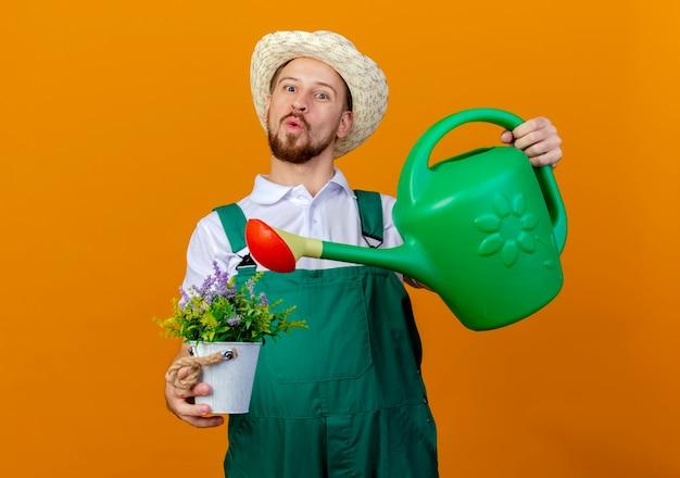 제복을 입은 젊은 잘 생긴 슬라브 정원사와 화분을 들고 모자를 쓰고 물을 수 있습니다.
