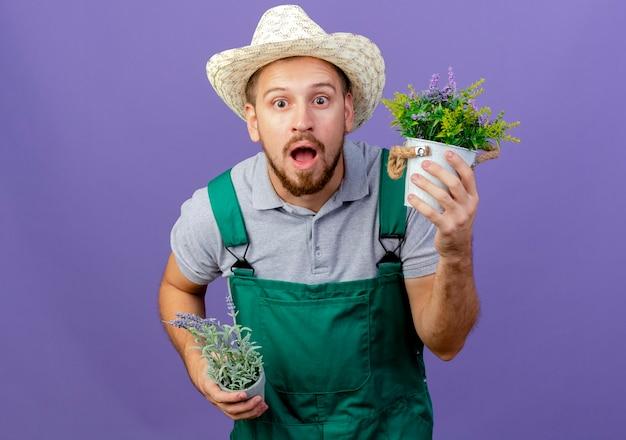 コピースペースと紫色の壁に分離された植木鉢を保持している制服と帽子の印象的な若いハンサムなスラブの庭師