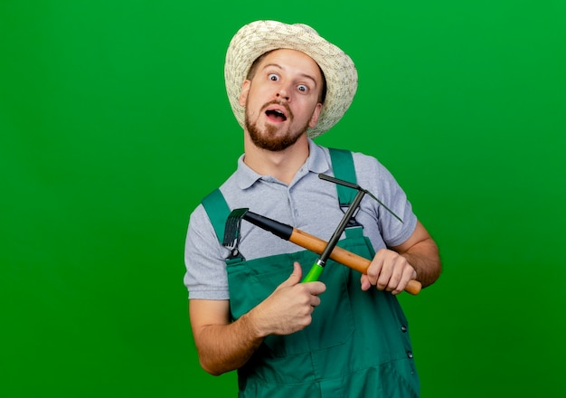 Впечатленный молодой красивый славянский садовник в униформе и шляпе, держащий грабли и грабли