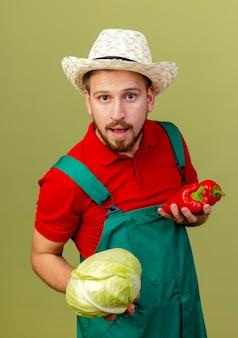 ピーマンとキャベツを探している制服と帽子を持った若いハンサムなスラブの庭師に感銘を受けました