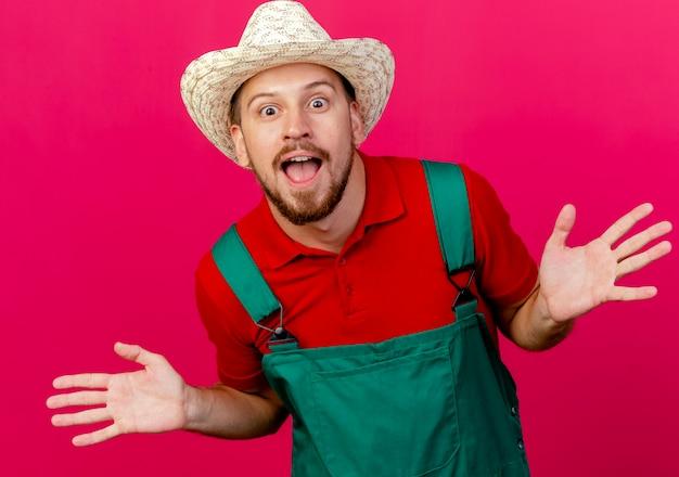 Впечатленный молодой красивый славянский садовник в униформе и шляпе, глядя, показывая пустые руки