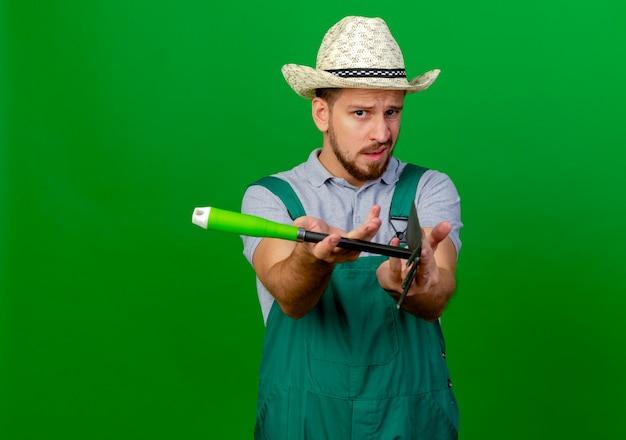 Впечатленный молодой красивый славянский садовник в униформе и шляпе смотрит, протягивая грабли