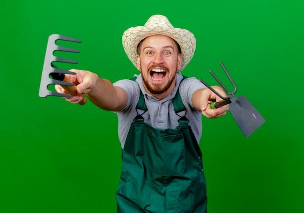 Впечатленный молодой красивый славянский садовник в форме и шляпе протягивает грабли и грабли в сторону