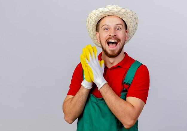 ガーデニングの手袋と帽子を身に着けている制服を着た若いハンサムなスラブの庭師は、手を一緒に隔離して見ていることに感銘を受けました