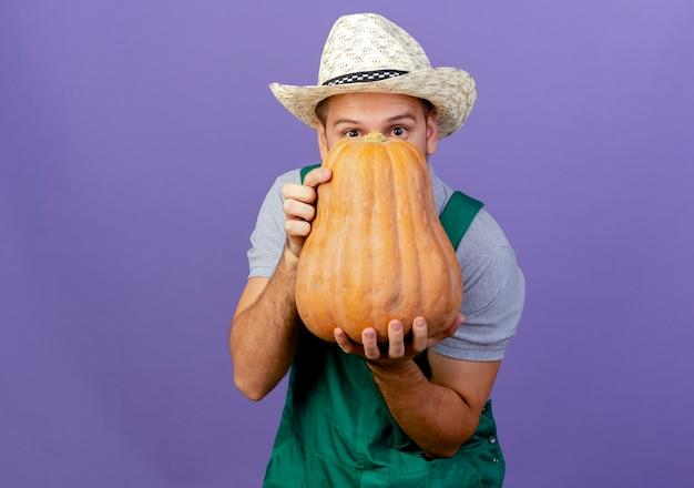 Impressionato giovane giardiniere slavo bello in uniforme e cappello che tiene zucca butternut guardando da dietro isolato