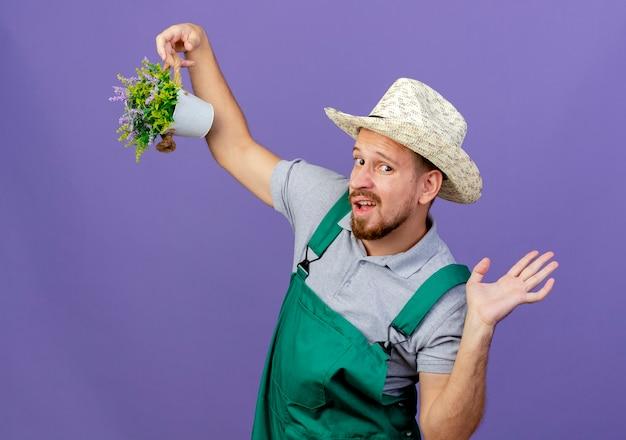 Impressionato giovane giardiniere slavo bello in uniforme e cappello che tiene vaso di fiori che guarda mostrando la mano vuota isolata sulla parete viola