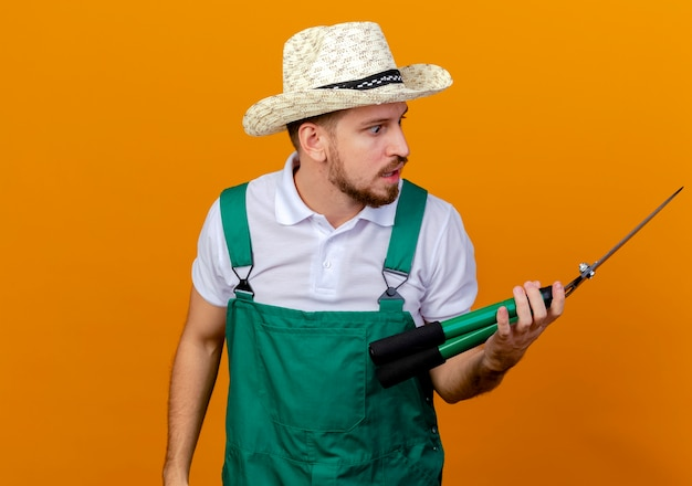 Impressed young handsome slavic gardener in uniform and hat holding and looking at pruners isolated on orange wall with copy space