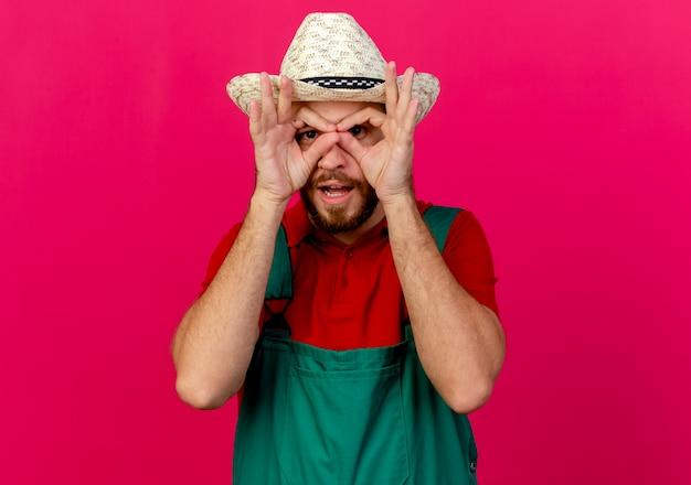 Impressionato giovane giardiniere slavo bello in uniforme e cappello che osserva facendo gesto di sguardo usando le mani come binocolo