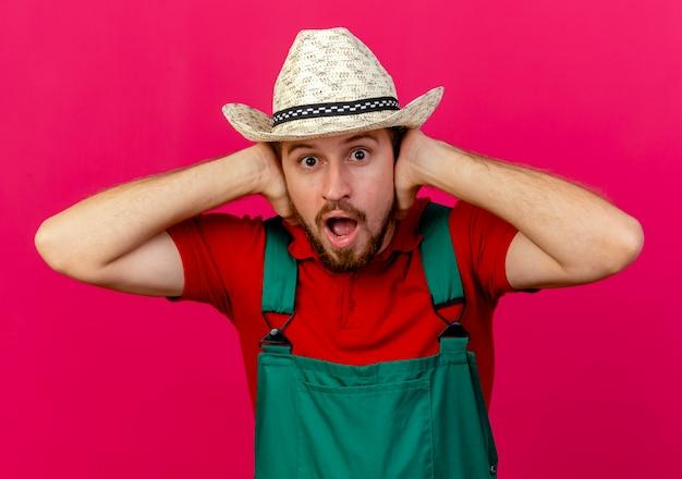 Impressionato giovane giardiniere slavo bello in uniforme e cappello cercando di mettere le mani sulle orecchie