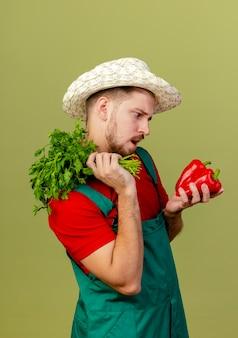 Impressionato giovane giardiniere slavo bello in uniforme e cappello in piedi in vista di profilo che tiene il coriandolo sulla spalla e peperoni guardando i peperoni isolati sulla parete verde oliva
