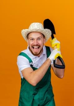 Giovane giardiniere slavo bello impressionato in cappello da portare uniforme e guanti di giardinaggio che tengono la vanga che sembra isolata