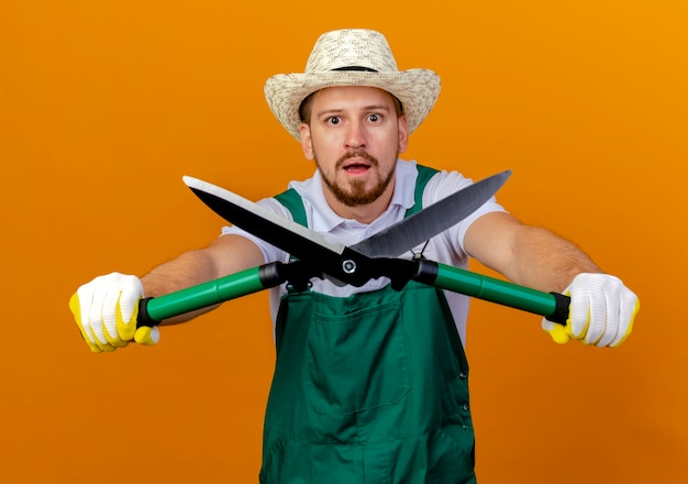 Impressed young handsome slavic gardener in uniform wearing hat and gardening gloves stretching out pruners towards isolated