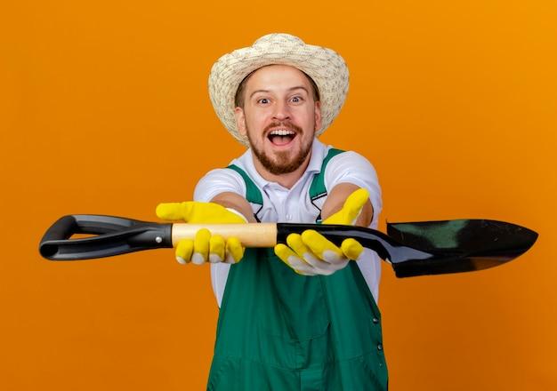 Impressionato giovane giardiniere slavo bello in uniforme che indossa cappello e guanti da giardinaggio che allungano vanga verso isolato