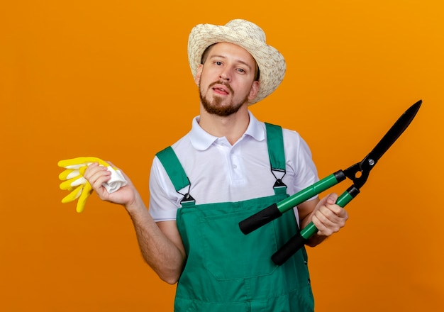 Impressed young handsome slavic gardener in uniform wearing hat holding gardening gloves and pruners looking  isolated on orange wall