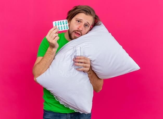 ピンクの壁に隔離されたカプセルと水のガラスのパックを保持している正面を見て枕を抱き締める若いハンサムなスラブの病気の男に感銘を受けました