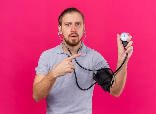 聴診器を身に着けている感銘を受けた若いハンサムなスラブ病の男性は、コピースペースでピンクの壁に隔離された正面を見て血圧計を指して彼の圧力を測定します