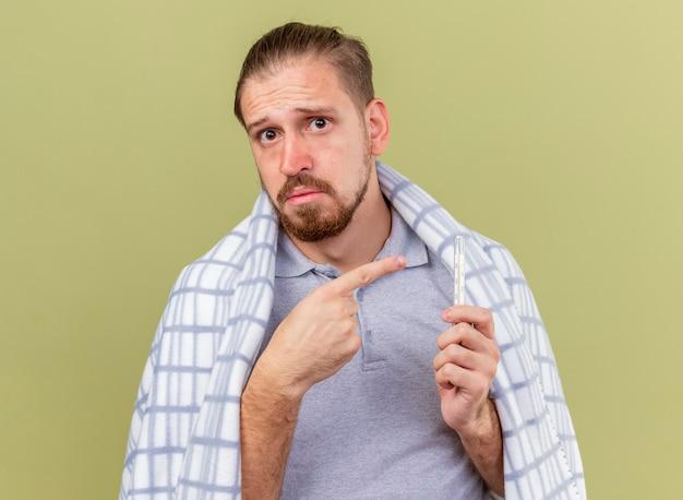 オリーブグリーンの壁に隔離された温度計を保持し、指している格子縞に包まれた感動の若いハンサムなスラブ病人