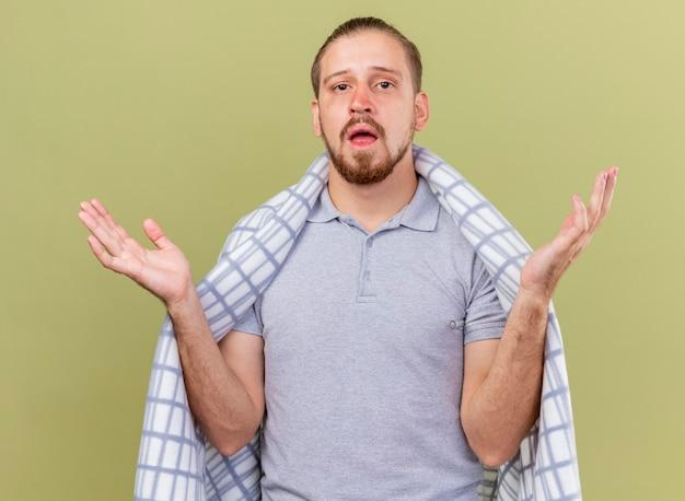 オリーブグリーンの背景で隔離の空の手を示すカメラを見て格子縞に包まれた印象的な若いハンサムなスラブの病気の男