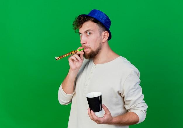Ragazzo di partito slavo bello colpito giovane che indossa il cappello del partito che soffia ventilatore del partito che tiene tazza di caffè di plastica isolata su fondo verde con lo spazio della copia