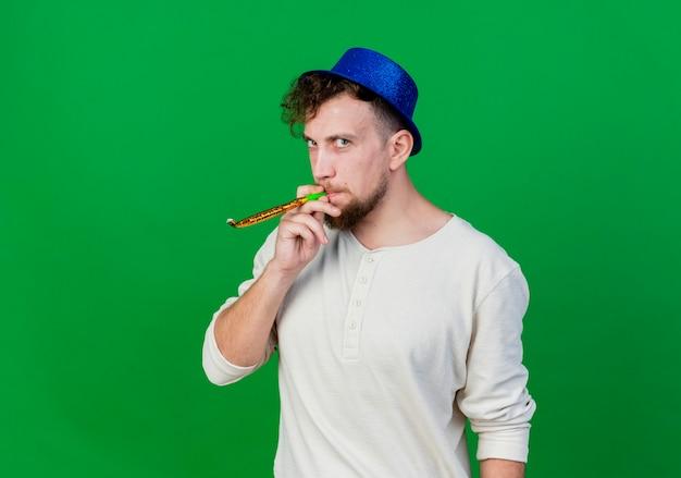 Впечатленный молодой красивый славянский партийный парень в партийной шляпе, дует вечеринку, глядя в камеру, изолированную на зеленом фоне с копией пространства