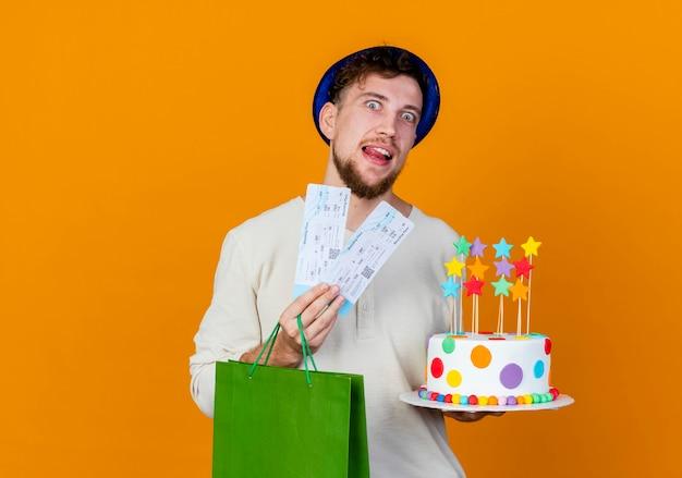 복사 공간 오렌지 배경에 고립 된 카메라를보고 별 비행기 티켓 종이 가방과 생일 케이크를 들고 파티 모자를 쓰고 감동 젊은 잘 생긴 슬라브 파티 남자