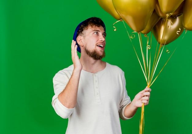 Впечатленный молодой красивый славянский тусовщик в партийной шляпе, держащий и смотрящий на воздушные шары, держа руку в воздухе, изолированную на зеленом фоне с копией пространства
