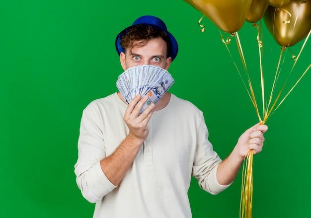 복사 공간이 녹색 배경에 고립 된 돈 뒤에서 카메라를보고 풍선과 돈을 들고 파티 모자를 쓰고 감동 젊은 잘 생긴 슬라브 파티 남자