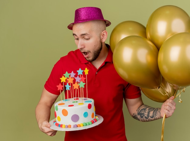 Impressed young handsome slavic party guy wearing party hat holding balloons and birthday cake looking at cake isolated on olive green background