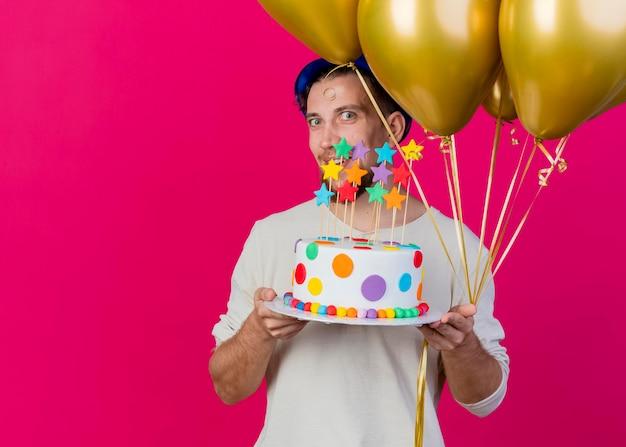 Impressionato giovane ragazzo slavo bello del partito che indossa il cappello del partito che tiene i palloncini e la torta di compleanno con le stelle che esaminano la parte anteriore isolata sulla parete rosa con lo spazio della copia