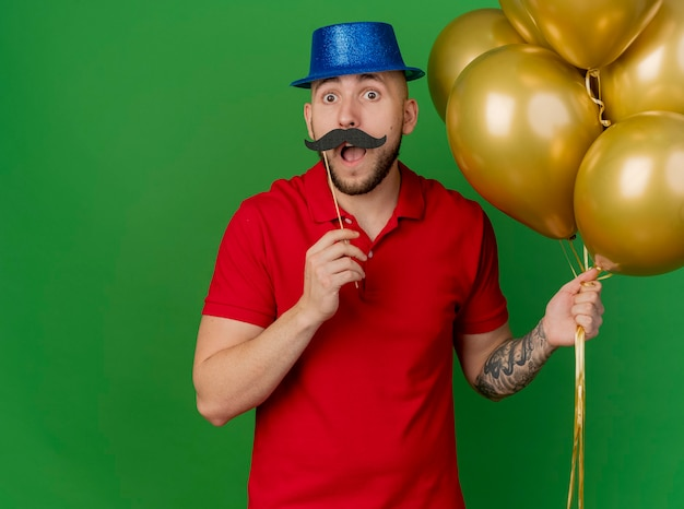 Impressed young handsome slavic party guy wearing party hat holding balloons and fake mustache on stick above lips looking at camera isolated on green background with copy space