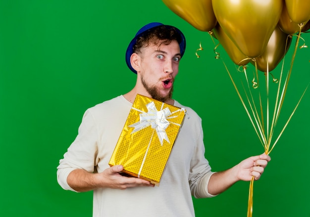 Impressed young handsome slavic party guy wearing party hat holding balloons and gift box looking at camera isolated on green background