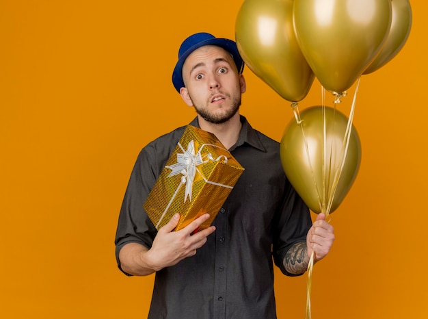 Impressed young handsome slavic party guy wearing party hat holding balloons and gift pack looking at camera isolated on orange background with copy space