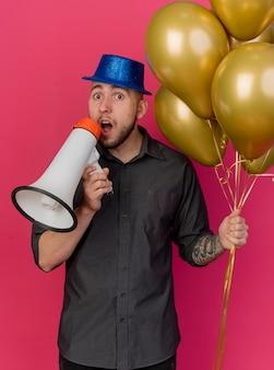 진홍색 배경에 고립 된 카메라를보고 입 근처 스피커를 들고 풍선을 들고 파티 모자를 쓰고 감동 젊은 잘 생긴 슬라브 파티 남자