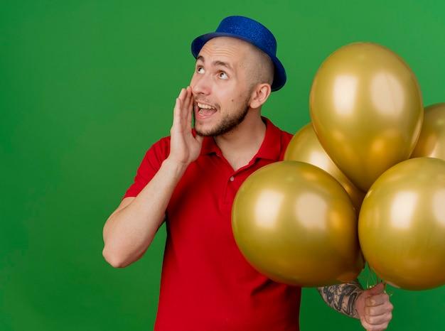 녹색 배경에 고립 속삭이는 측면을보고 풍선을 들고 파티 모자를 쓰고 감동 젊은 잘 생긴 슬라브 파티 남자