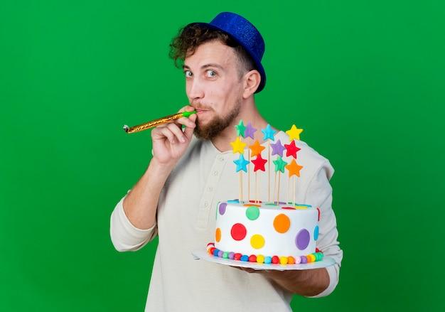 Ragazzo di partito slavo bello impressionato che indossa il cappello del partito che tiene la torta di compleanno con le stelle che soffia il ventilatore del partito che guarda l'obbiettivo isolato su priorità bassa verde con lo spazio della copia