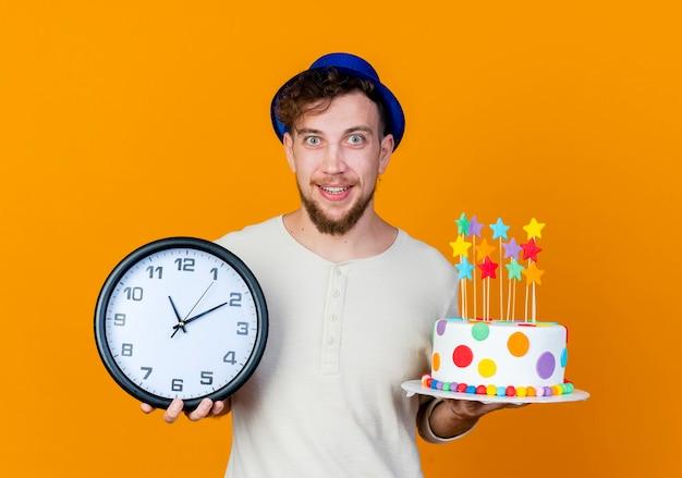 オレンジ色の背景に分離されたカメラを見て星と時計とバースデーケーキを保持しているパーティーハットを身に着けている感動若いハンサムなスラブパーティー男
