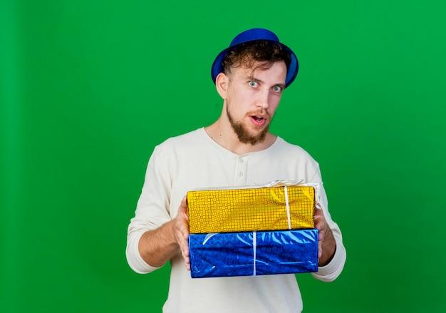 Impressionato giovane ragazzo slavo bello del partito che indossa il cappello del partito che tiene i contenitori di regalo che esaminano la parte anteriore isolata sulla parete verde con lo spazio della copia
