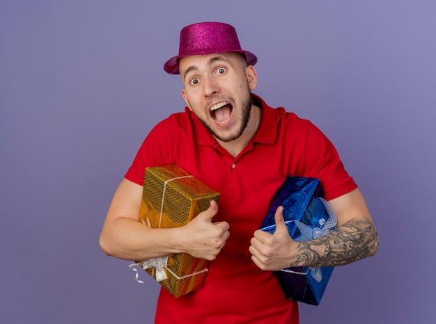コピースペースで紫色の背景に分離されたカメラを見てギフトパックを保持しているパーティーハットを身に着けている感動の若いハンサムなスラブ党の男
