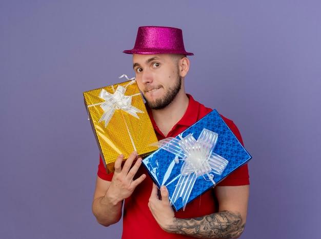 Impressionato giovane ragazzo slavo bello del partito che indossa il cappello del partito che tiene confezioni regalo guardando la fotocamera che morde il labbro isolato su sfondo viola con spazio di copia