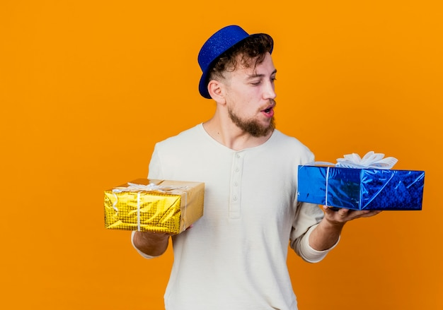 Impressed young handsome slavic party guy wearing party hat holding and looking at gift boxes isolated on orange background with copy space