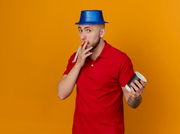 コピースペースでオレンジ色の背景に分離された手にプラスチック製のコーヒーカップと口の中でパーティーブロワーを保持しているカメラを見てパーティー帽子をかぶっている感動の若いハンサムなスラブパーティー男