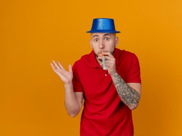 コピースペースでオレンジ色の背景に分離された空の手吹くパーティーブロワーを示すカメラを見てパーティー帽子をかぶっている感動の若いハンサムなスラブパーティー男