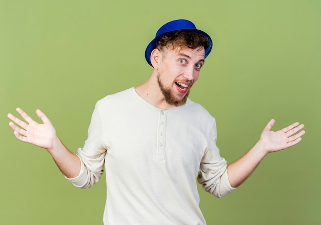 オリーブグリーンの背景で隔離の空の手を示すカメラを見てパーティー帽子をかぶって感動の若いハンサムなスラブパーティー