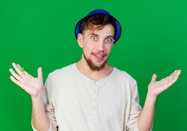 緑の壁に隔離された空の手を示す正面を見てパーティー帽子をかぶって感動した若いハンサムなスラブ党の男