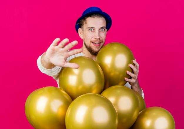 Ragazzo di partito slavo bello impressionato che indossa il cappello del partito in piedi dietro i palloncini che mette la mano sul palloncino che allunga la mano e che guarda l'obbiettivo isolato su priorità bassa cremisi