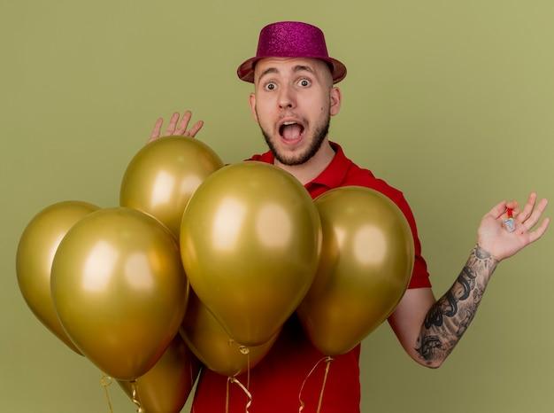 올리브 녹색 배경에 고립 된 빈 손을 보여주는 카메라를보고 풍선 뒤에 서있는 파티 모자를 쓰고 감동 젊은 잘 생긴 슬라브 파티 남자