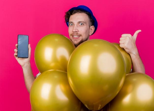 Впечатленный молодой красивый славянский тусовщик в партийной шляпе, стоящий за воздушными шарами, глядя вперед, показывая мобильный телефон и большой палец вверх изолирован на розовой стене