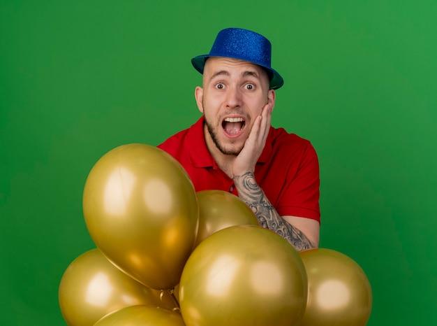 녹색 배경에 고립 된 카메라를보고 얼굴을 만지고 풍선 뒤에 서있는 파티 모자를 쓰고 감동 젊은 잘 생긴 슬라브 파티 남자