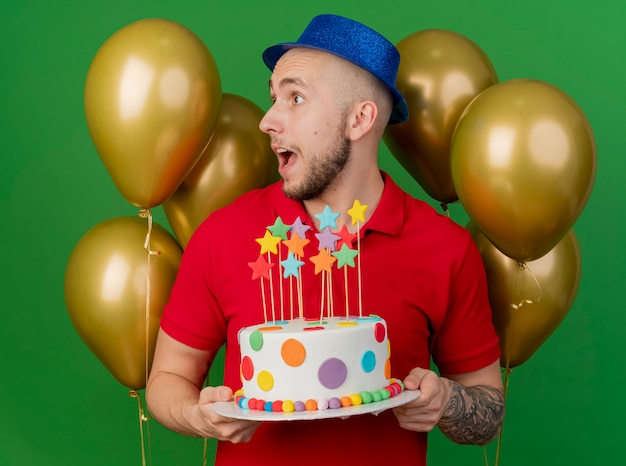 Impressed young handsome slavic party guy wearing party hat standing in front of balloons holding birthday cake looking at side isolated on green background