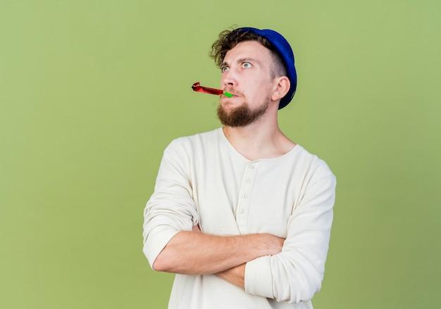 コピースペースでオリーブグリーンの背景に分離された口の中でパーティーブロワーで横を見て閉じた姿勢で立っているパーティーハットを身に着けている印象的な若いハンサムなスラブパーティー男